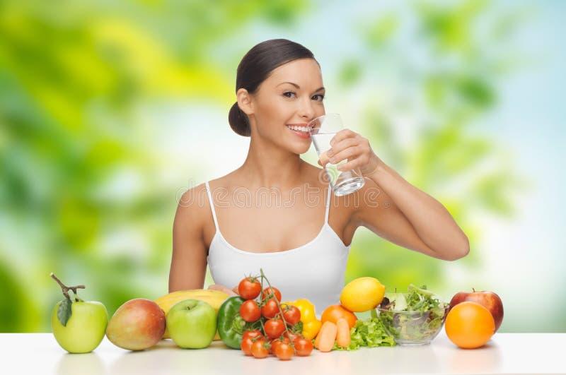 Kobieta z zdrowym jedzeniem na stołowej wodzie pitnej fotografia stock