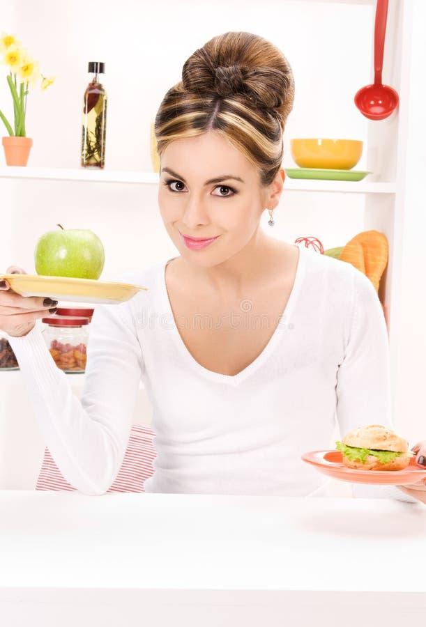 Kobieta z zielonym jabłkiem i kanapką zdjęcia royalty free