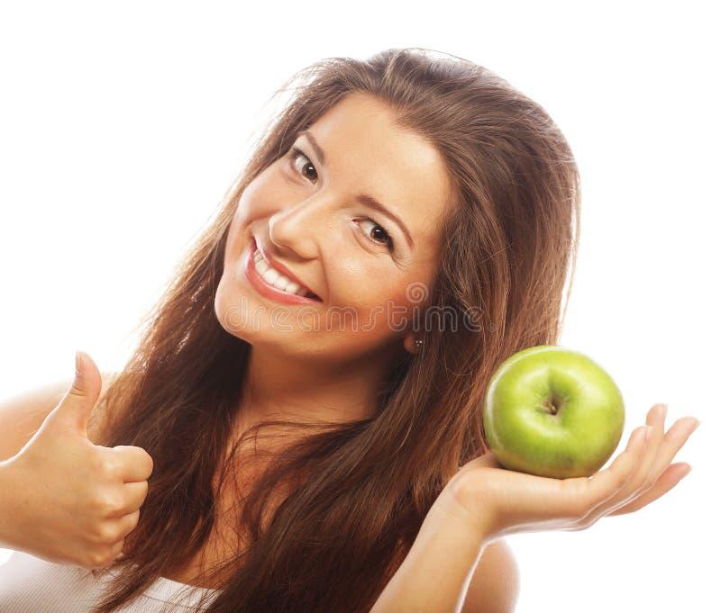 Kobieta z zielonym jabłkiem i pokazywać up kciukiem obrazy stock