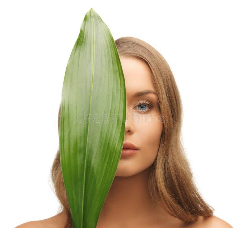 Kobieta z zielonym liściem zdjęcia stock