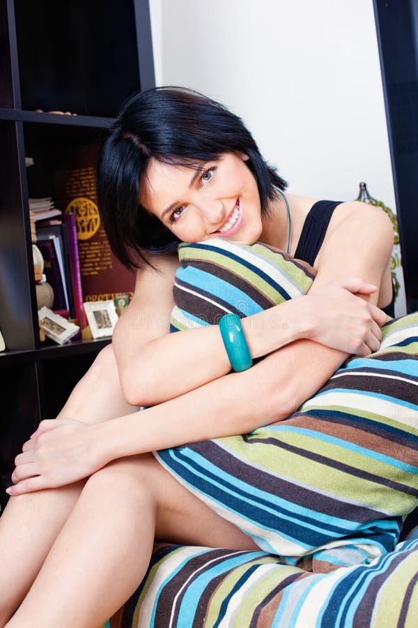 Kobieta za poduszką w domu zdjęcie royalty free