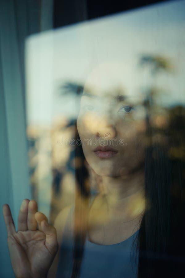 Kobieta za szklanym okno obrazy stock