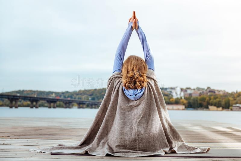 Kobieta zakrywająca z brąz szkockiej kraty ćwiczy medytacją obrazy stock