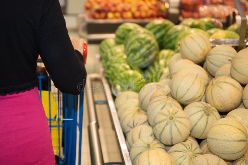 Kobieta zakupy dla sklepów spożywczych w supermarket pozyci z ona z powrotem fotografia royalty free