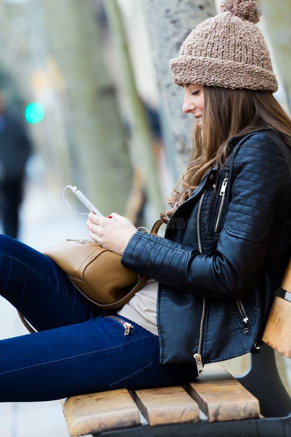 Kobieta zakupy w mieście z jego smartphone zdjęcie royalty free