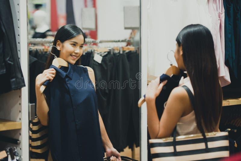 Kobieta zakupy wybiera suknie patrzeje w lustrzany niepewnym fotografia stock