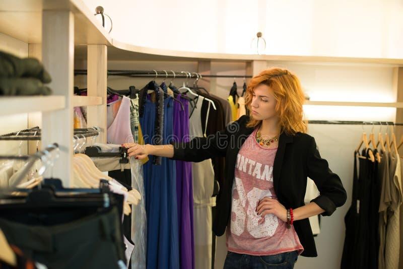 Kobieta zakupy wybiera suknie patrzeje w lustrzany niepewnym fotografia royalty free