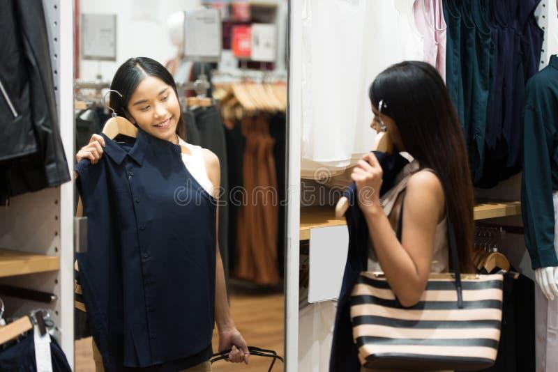 Kobieta zakupy wybiera suknie patrzeje w lustrzany niepewnym bea fotografia royalty free
