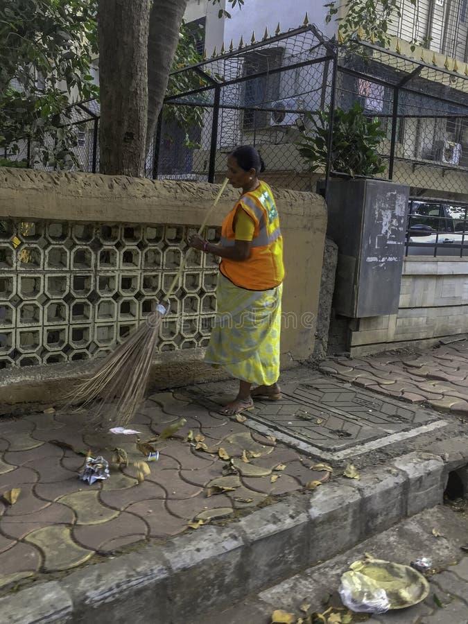 Kobieta zamiata bruk w Mumbai India zdjęcie stock