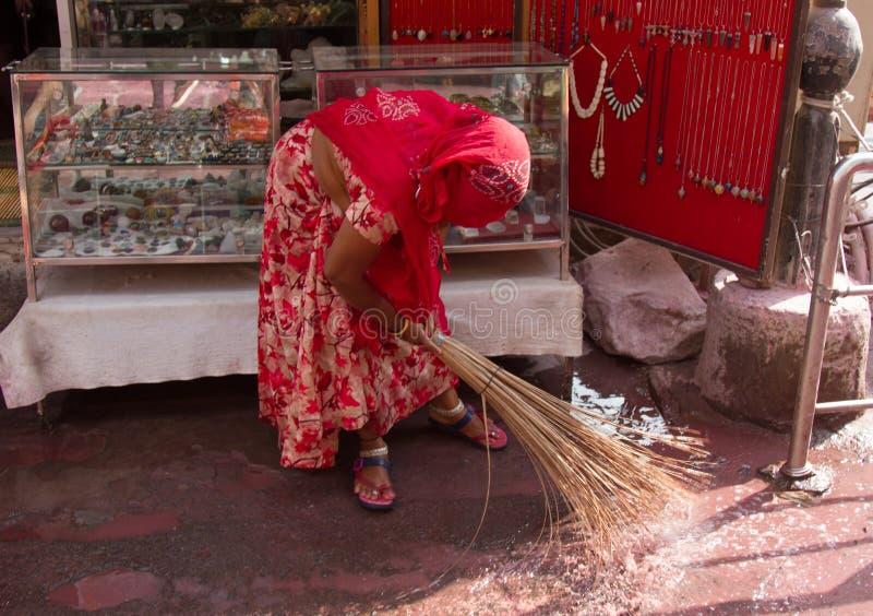 Kobieta zamiata przed tacą z towarami obrazy stock
