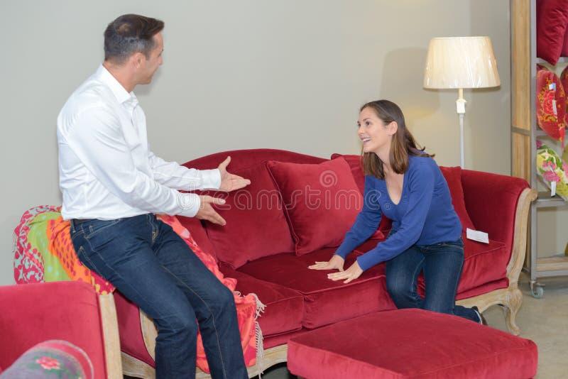 Kobieta zapraszający mężczyzna badać kanapę z zdjęcia stock