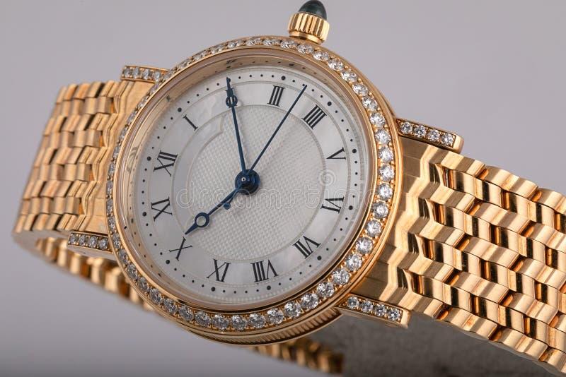 Kobieta zegarek z złocistą metal patką, diamenty z białą tarczą, czerni liczby i błękit, wręcza odosobnionego na białym tle obrazy royalty free
