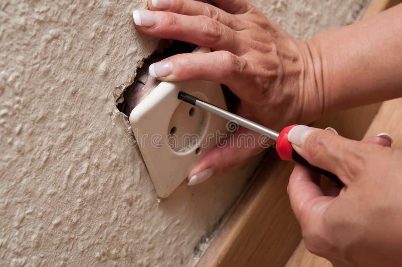 Kobieta zmienia elektrycznego ujście obrazy stock