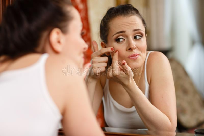Kobieta znajduje trądzika na jej policzku obraz stock