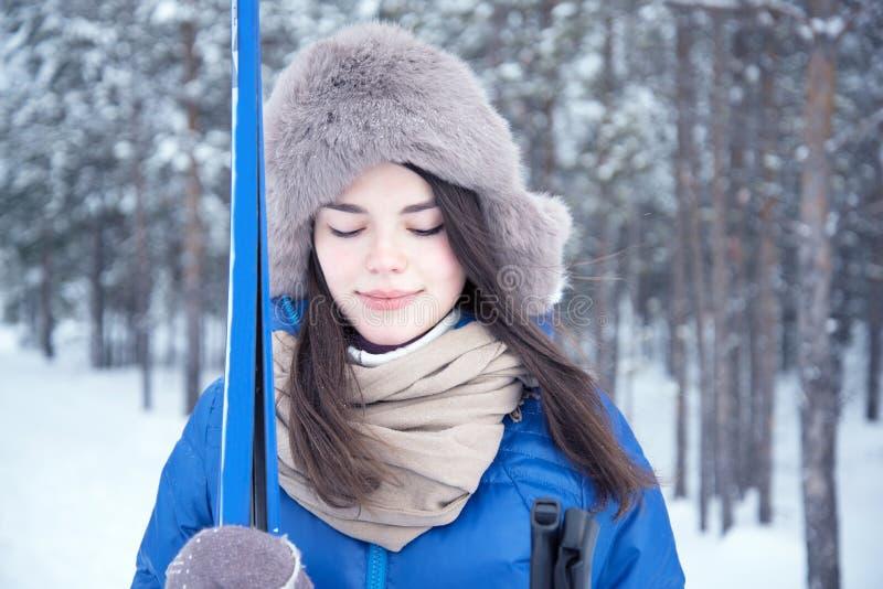 Kobieta zostaje z nartą w drewnach fotografia royalty free