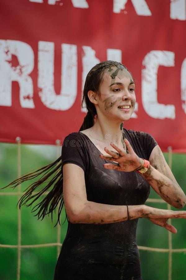 Kobieta zwycięzca brać miejsce w Kijów, po tym jak pokonuje wodną borowinową barierę podczas władzy rasy legii bieg zdjęcie royalty free