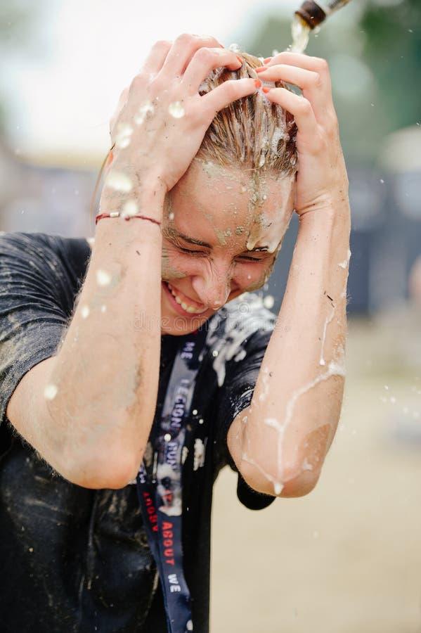 Kobieta zwycięzca brać miejsce w Kijów, po tym jak pokonuje wodną borowinową barierę podczas władzy rasy legii bieg obraz royalty free