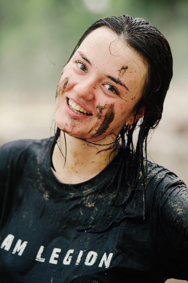 Kobieta zwycięzca brać miejsce w Kijów, po tym jak pokonuje wodną borowinową barierę podczas władzy rasy legii bieg fotografia royalty free