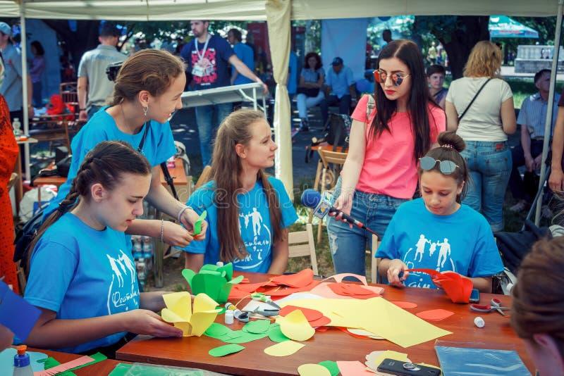 Kobiety †'dziennikarz przeprowadza wywiad nastoletnie dziewczyny, uczestniczy w robić kolorowych papierowych kwiaty warsztatowi obraz royalty free