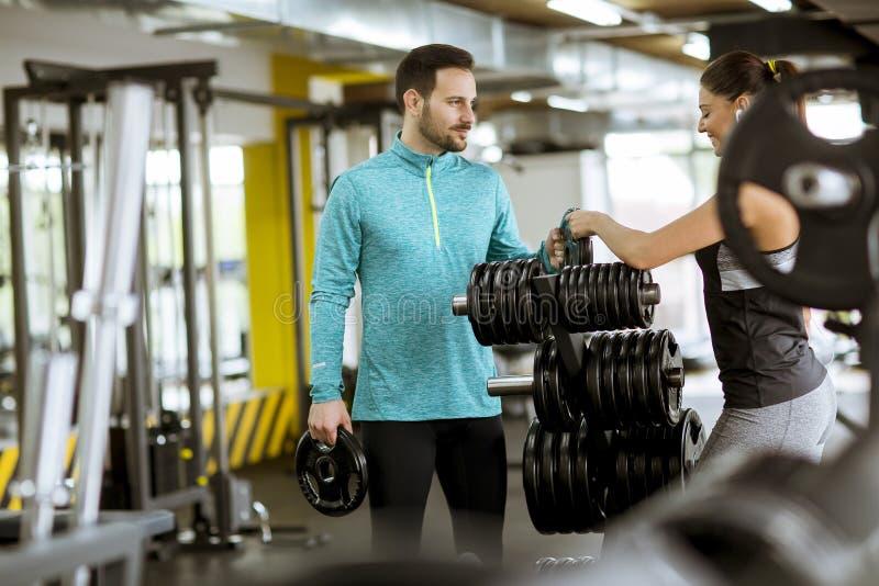 Kobiety ćwiczenie w gym z pomocą jej osobistego trenera zdjęcia royalty free