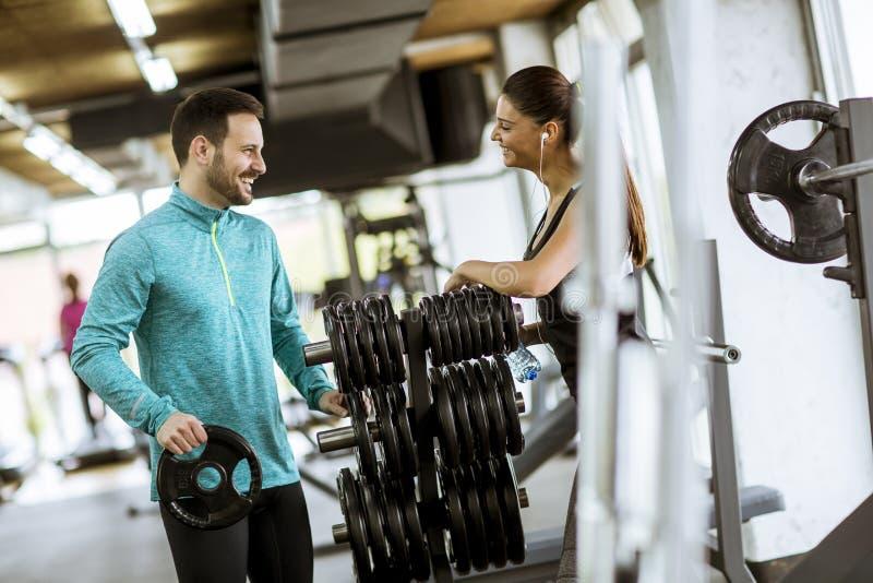 Kobiety ćwiczenie w gym z pomocą jej osobistego trenera obrazy royalty free