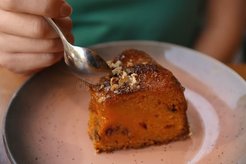 Kobiety łasowania plasterek marchwiany tort przy stołem obraz stock