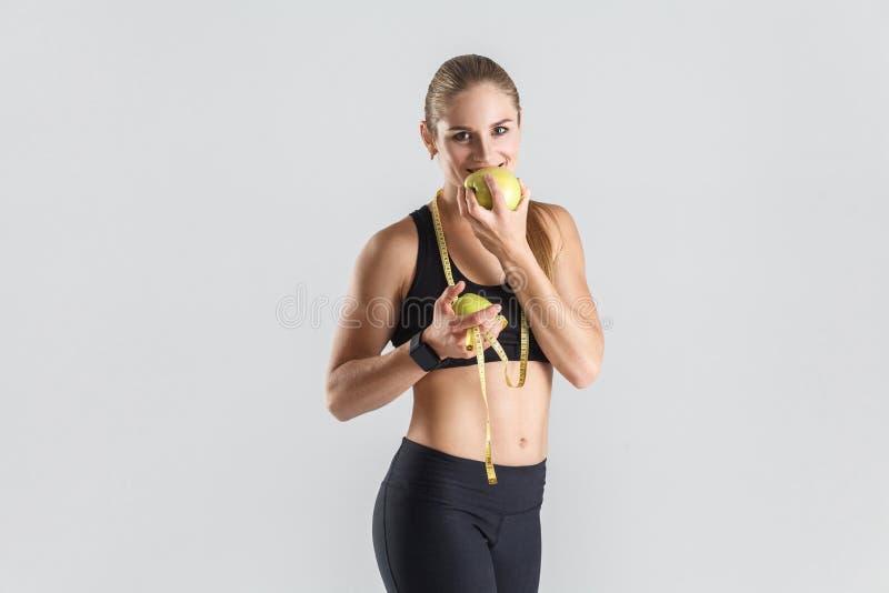 Kobiety łasowania zieleni jabłko, toothy kamera, uśmiechnięta i patrzeje zdjęcie stock