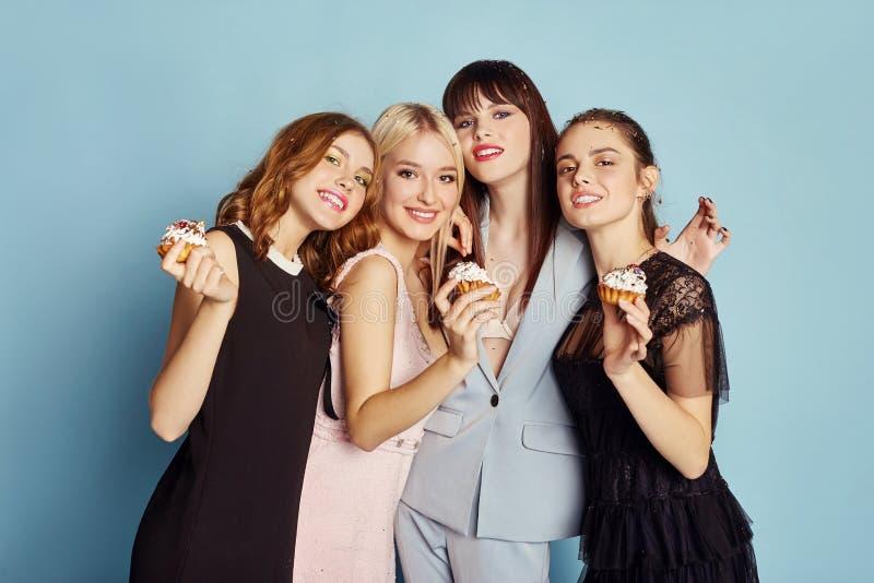 Kobiety śmia się świętują wakacyjnego przyjęcia ma zabawę i jeść zasycha pod latającymi confetti Dziewczyny pozuje i ono uśmiecha zdjęcia royalty free
