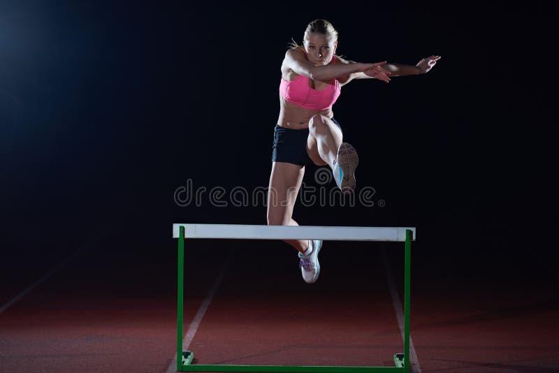 Kobiety atleta skacze nad przeszkody zdjęcia stock