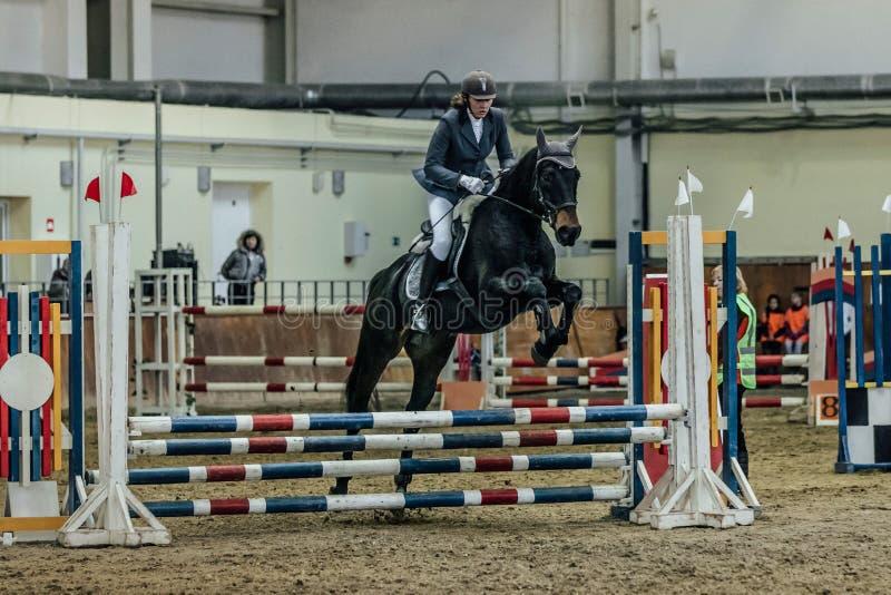 Kobiety atlety jeźdza koń pokonuje przeszkoda sportów kompleks indoors fotografia royalty free