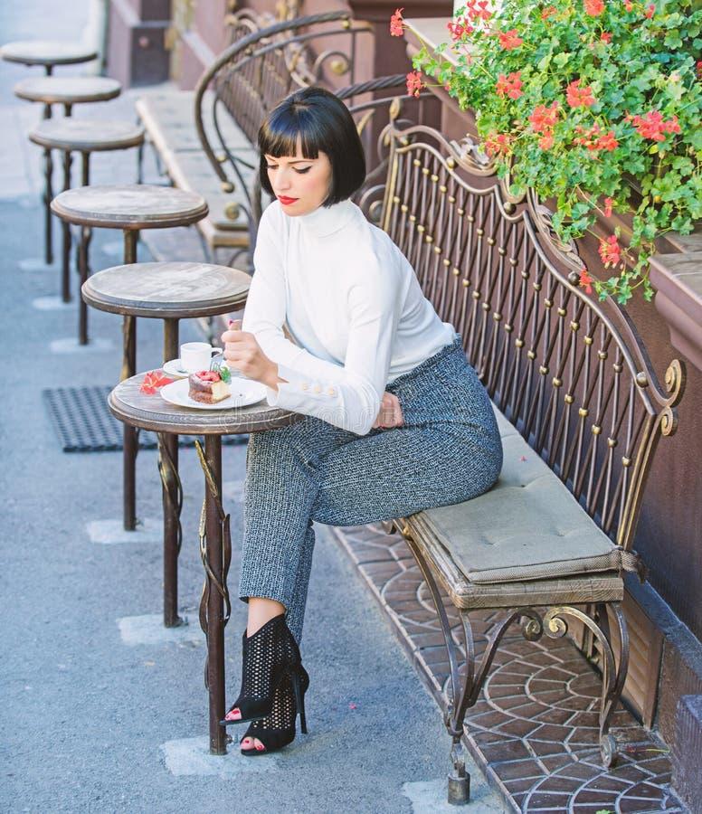 Kobiety atrakcyjna brunetka je smakosz kawiarni tarasu tortowego t?o Gastronomical przyjemno?? Dziewczyna relaksuje kawiarni z to obraz stock