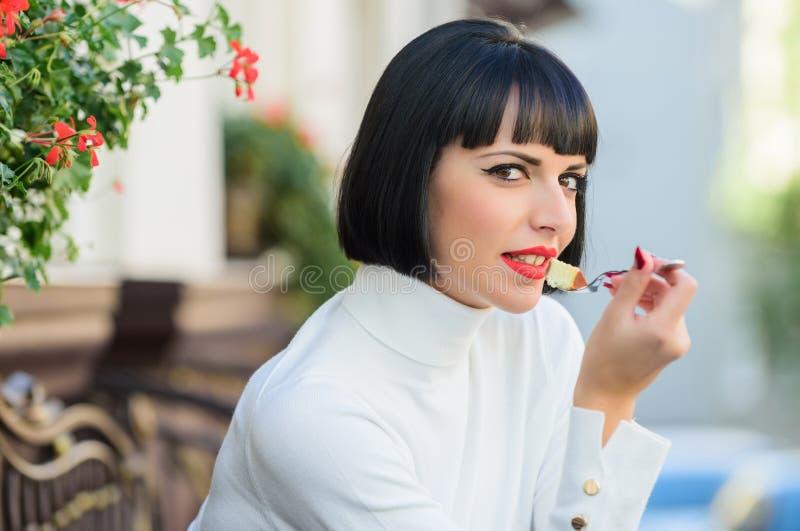 Kobiety atrakcyjna elegancka brunetka je smakosz kawiarni tarasu tortowego t?o Pamper Dziewczyna relaksuje kawiarni z tortem zdjęcie royalty free