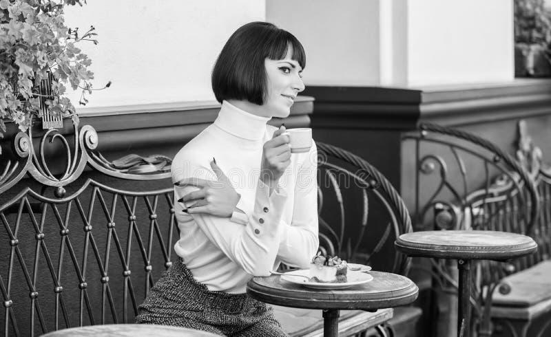 Kobiety atrakcyjna elegancka brunetka je smakosz kawiarni tarasu tortowego t?o Przyjemny czas i relaks deliciouses zdjęcia stock