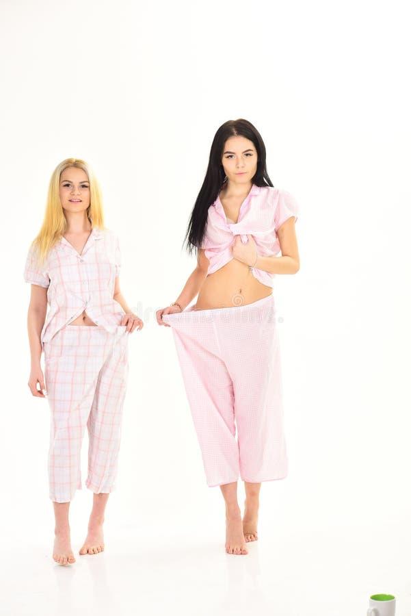 Kobiety, atrakcyjne młode siostry, przyjaciele w piżamach Ciężar straty rezultata pojęcie Dziewczyny na zadumanej twarzy pokazują fotografia stock