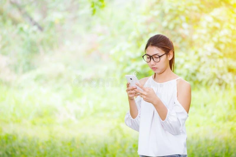 Kobiety bawić się telefon w parku i są ubranym biel suknię fotografia royalty free
