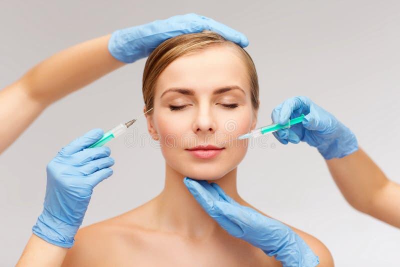 Kobiety beautician i twarzy ręki z strzykawką zdjęcia stock