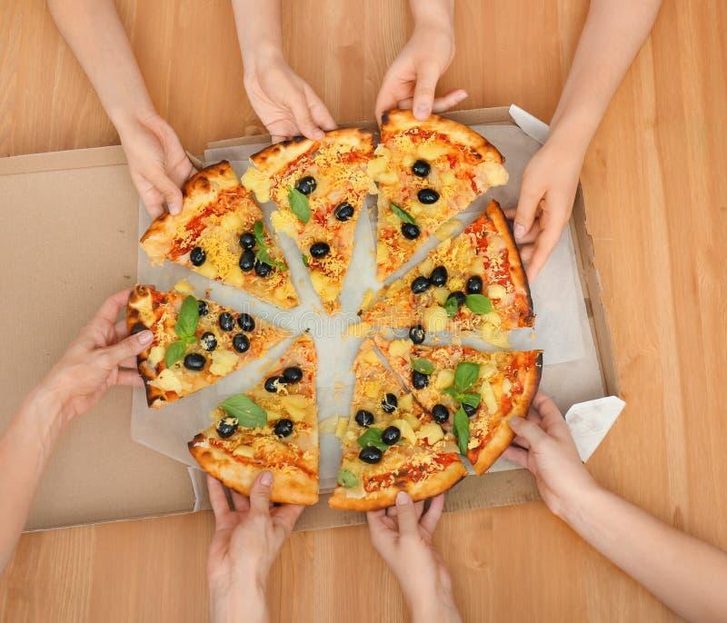 Kobiety bierze plasterki smakowita Włoska pizza od pudełka na drewnianym stole, odgórny widok zdjęcie royalty free