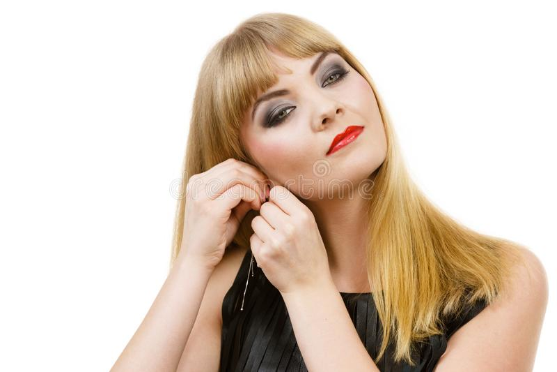 Kobiety blondynki damy elegancki kładzenie na kolczykach zdjęcia royalty free
