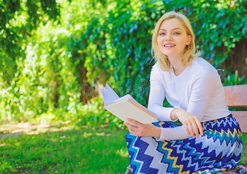 Kobiety blondynki wp8lywy szczęśliwa uśmiechnięta przerwa relaksuje w ogrodowej czytelniczej poezi Dziewczyna relaksuje z książką obrazy royalty free