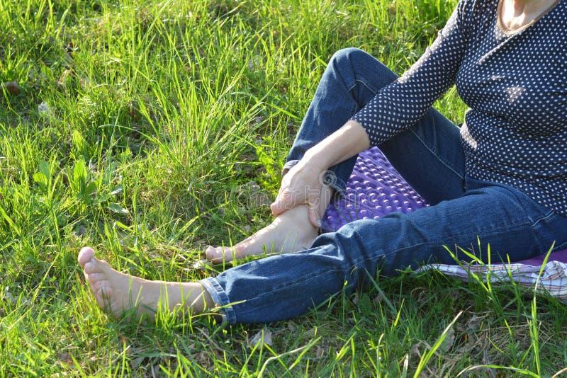 Kobiety bosy odpoczywać na zielonej trawy tle zdjęcie royalty free