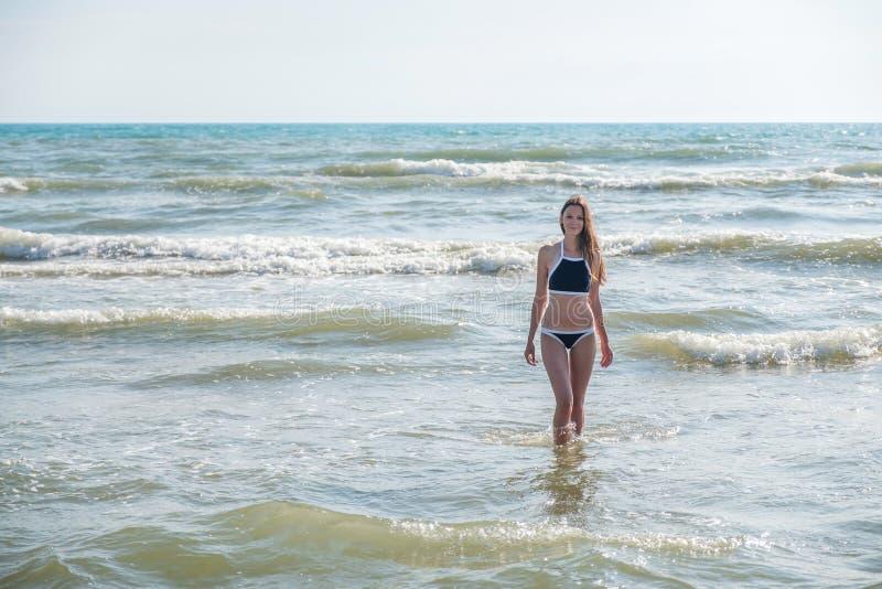 Kobiety bruenette z długie włosy w błękitnym bikini iść pływać w falowym ` s morzu Frontowy widok Zakończenie fotografia stock