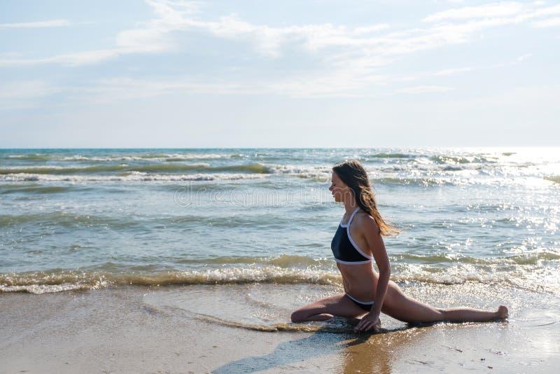 Kobiety bruenette z długimi hairs w błękitnym bikini rozciąga na seashore Boczny widok obrazy royalty free