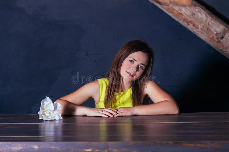 Kobiety brunetki bawełny sukni żółci niebieskie oczy kwitną lampowego błękitnego tło rocznika minimalizmu nieociosanego portreta  zdjęcie royalty free