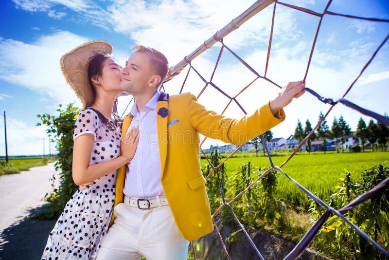 Kobiety całowania mężczyzna podczas gdy stojący ogrodzeniem przy polem przeciw niebu obraz royalty free