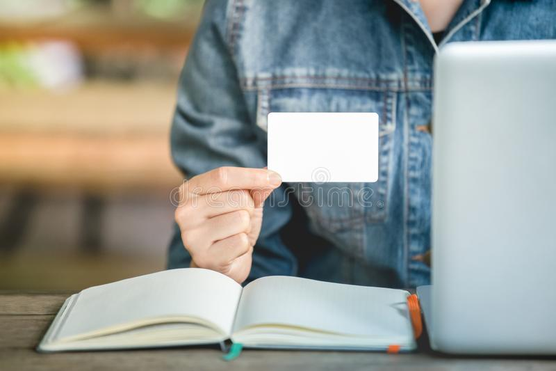 Kobiety Cajgowy jecket jest ręką trzyma białą wizytówkę dla kontaktowych prac Pusty papierowej karty egzamin próbny w górę zdjęcia royalty free