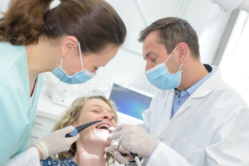 Kobiety chichotanie w dentysty ` s krześle fotografia stock