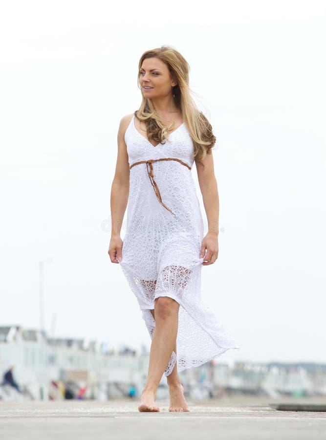 Kobiety chodzić bosy w biel sukni outdoors fotografia royalty free