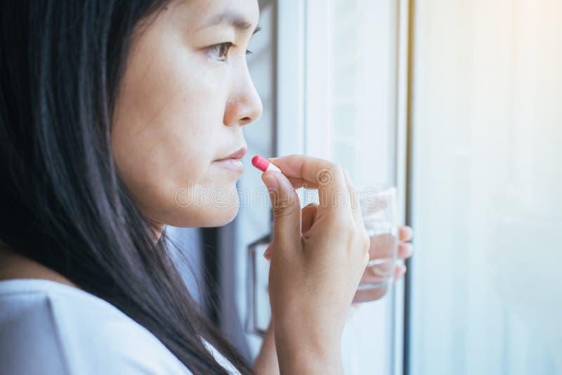 Kobiety choroba stawia w jej usta z kapsułami, kobieta bierze medycyny i szkło woda, pojęcie dla zdrowie obraz royalty free