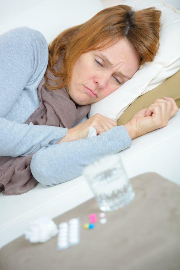 Kobiety choroba w łóżku z lekami na nightstand zdjęcie royalty free