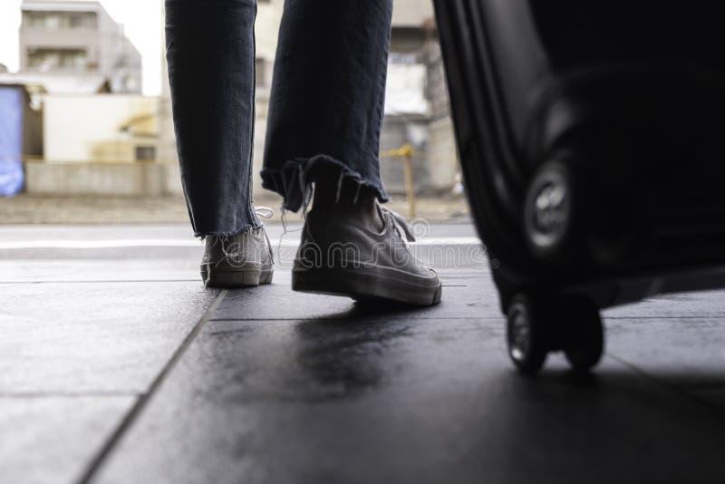 Kobiety cieki podczas gdy podróżujący czarnego bagaż w outdoors i wlec obrazy stock